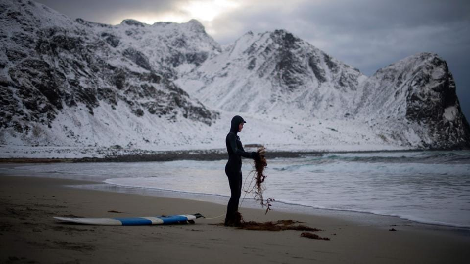 A novice surfer cleans his leash as he prepares for surfing. (Olivier Morin/AFP)