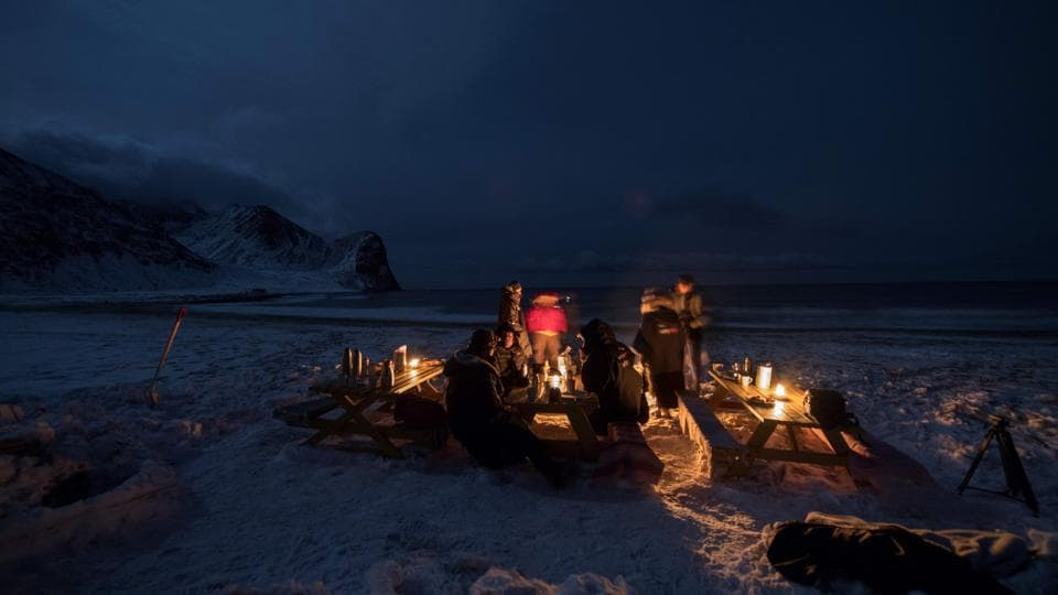 Surfers rest in front of a camp fire after an evening of surfing. (Olivier Morin/AFP)