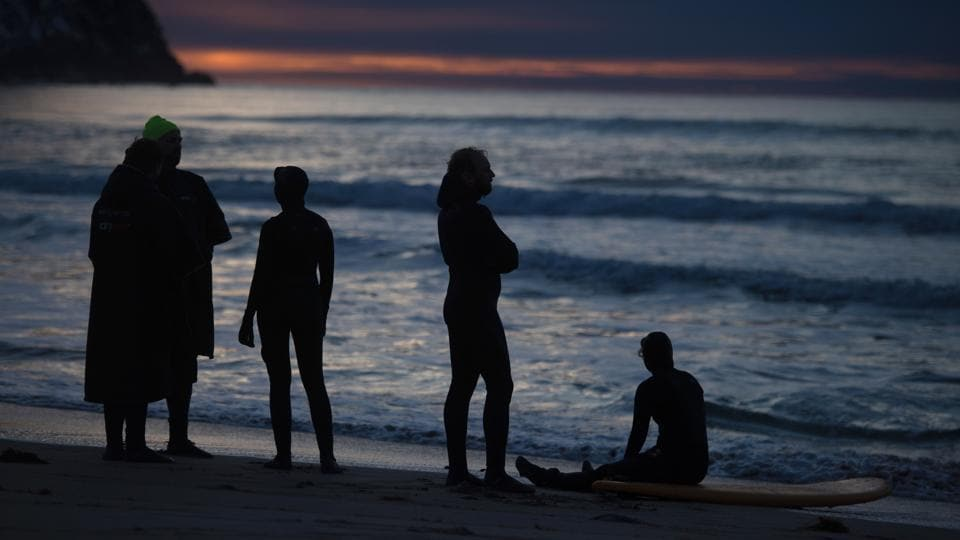 Surfers rest and enjoy the beautiful unset after surfing along the northern Atlantic Ocean. (Olivier Morin/AFP)