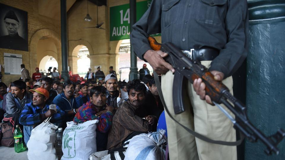 Indian fishermen are guarded by Pakistani security personnel after their release from prison, at a train station in Karachi on December 25, 2016. Pakistan had released 220 Indian fishermen held for trespassing into its territorial waters as a