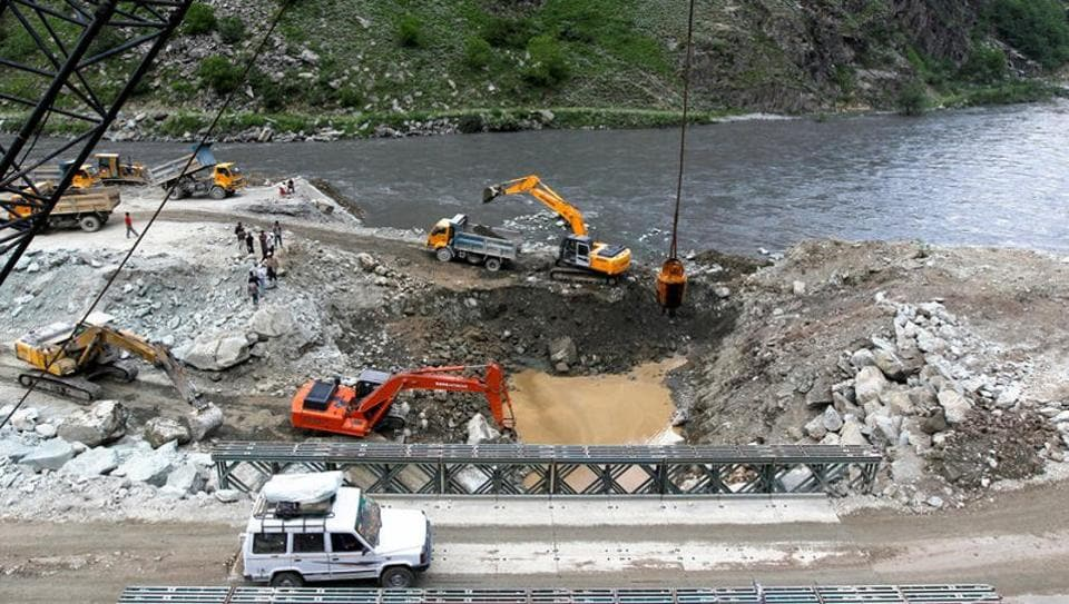 A private vehicle crosses a bridge as excavators are used at the dam site of Kishanganga power project in Gurez, 160 km north of Srinagar, in this file photo from June 21, 2012.