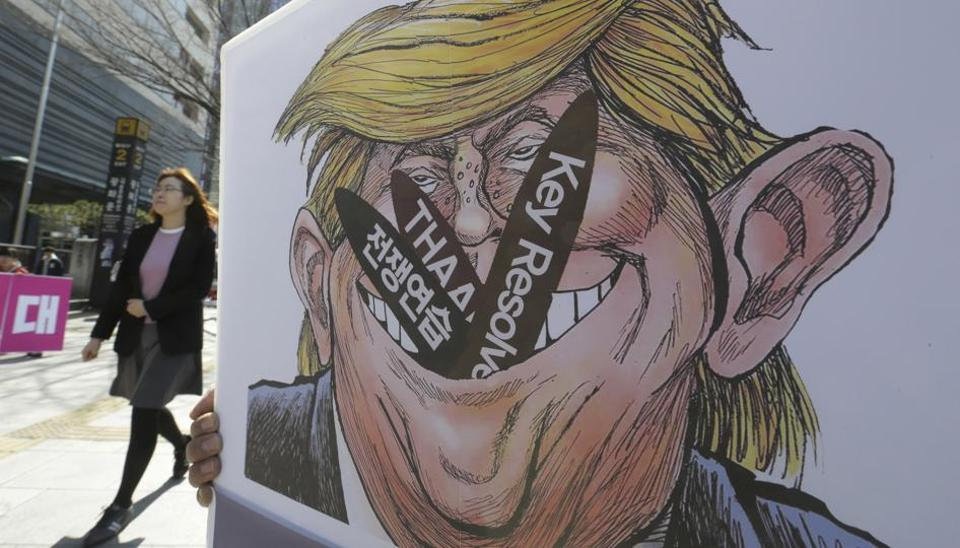 A woman walks by a poster with an illustration of US President Donald Trump held by a protester during a rally to oppose a plan to deploy an advanced US missile defence system called Terminal High-Altitude Area Defense (THAAD), near the US Embassy in Seoul, South Korea,  on March 14, 2017.