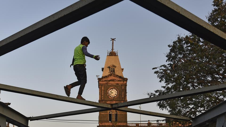 A child plays on a bridge in front of Ghadiyal Godi clock tower in Mumbai.