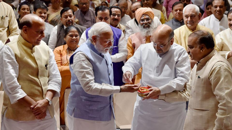 BJP president Amit Shah (second from right) offers sweets from the Tirupati temple to Prime Minister Narendra Modi as home minister Rajnath Singh (left) looks, on during the BJP parliamentary party meeting in New Delhi on Thursday.