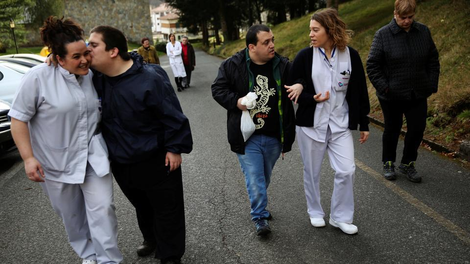 Inaki Gorriz (L) kisses social worker Irune Alchu, as Andres Garcia (C) walks hand in hand with nurse Andre Carricaburu while going for a walk with