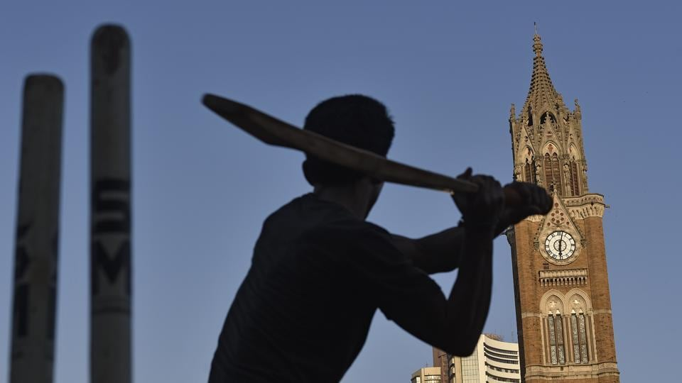 Young cricketers play against Rajabai ClockTower at Fort, among the few  working  clocks in Mumbai. (Vijayanand Gupta/HT Photo)