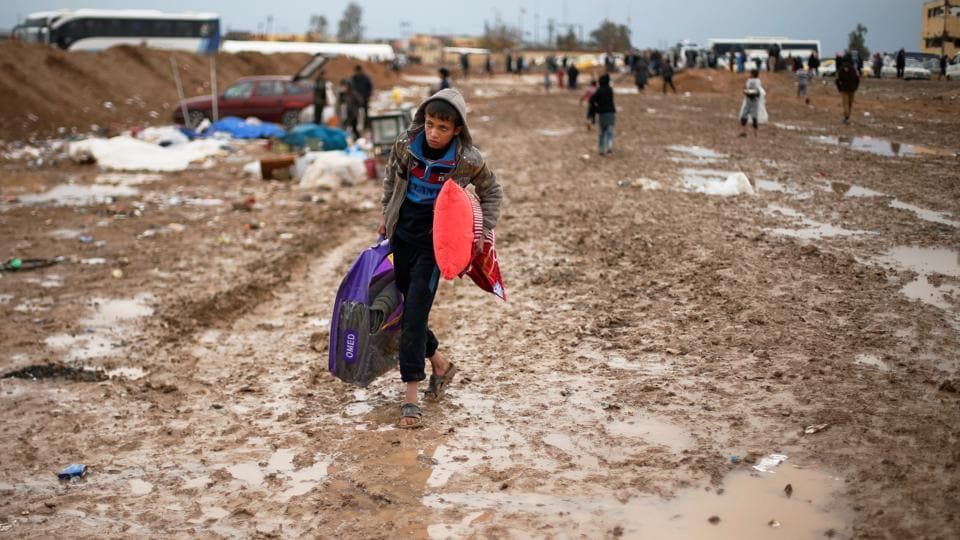 A displaced Iraqi makes his way to get into Hamam al-Alil camp, on a rainy day, south of Mosul. (Suhaib Salem / REUTERS)