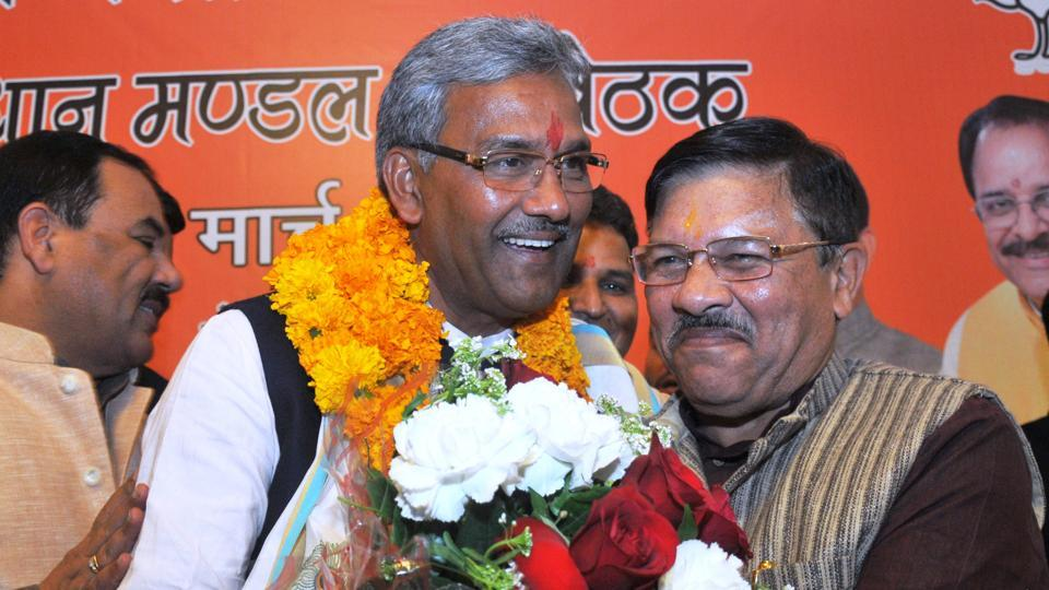 State BJP president Ajay Bhatt presents a bouquet to Trivendra Singh Rawat after the latter was nominated as the  new chief minister of Uttarakhand, in Dehradun on Friday.