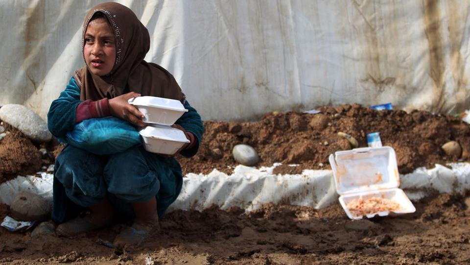 An Iraqi girl, displaced from Mosul, carries food rations as she sits near a tent at the Hammam al-Alil camp for the internally displaced, south of Mosul. (AHMAD AL-RUBAYE / AFP)