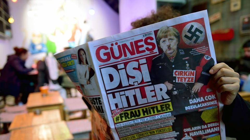 A man reads an issue of Gunes, a Turkish pro-government daily newspaper, with on its front page German Chancellor Angela Merkel depicted in Nazi uniform with a Hitler-style moustache, labelling the German leader 'She Hitler'.