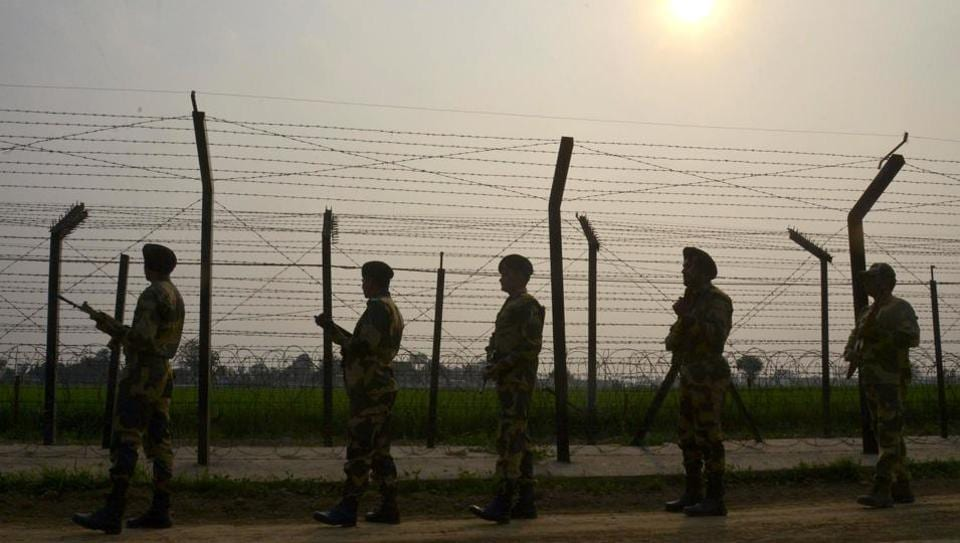 Border Security Force (BSF) personnel patrolling along a fence at the India-Pakistan border, at Wagah.