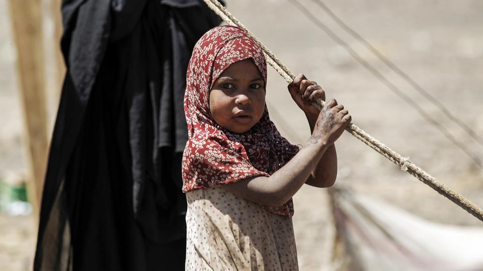 A Yemeni girl awaits humanitarian aid supplies given by the Russian humanitarian relief mission in a camp on the outskirts of the capital Sanaa. (MOHAMMED HUWAIS / AFP)