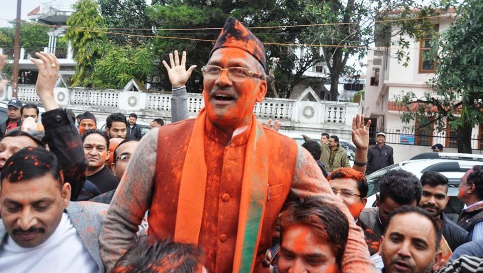 BJP workers hold BJP leader Trivendra Singh Rawat outside the BJP office in Dehradun following the party's poll victory on Saturday. He will be sworn in as the state's chief minister.