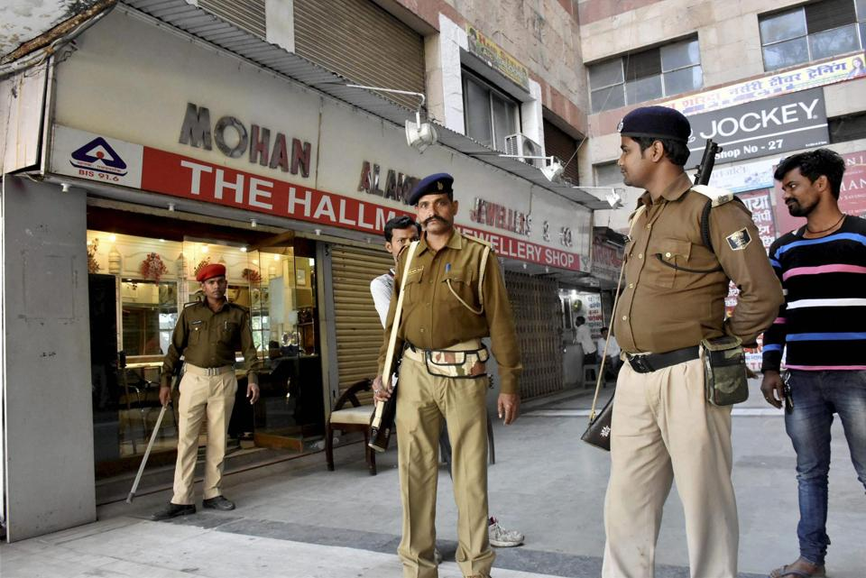 Policemen guard outside a jewellery shop during an IT raid in Patna on Wednesday. PTI Photo(PTI2_22_2017_000040B)