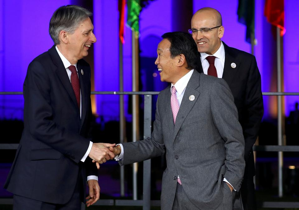 Japanese Finance Minister Taro Aso and Britain's Chancellor of the Exchequer Philip Hammond arrive for the family photo at the G20 Finance Ministers and Central Bank Governors Meeting in Baden-Baden, Germany.