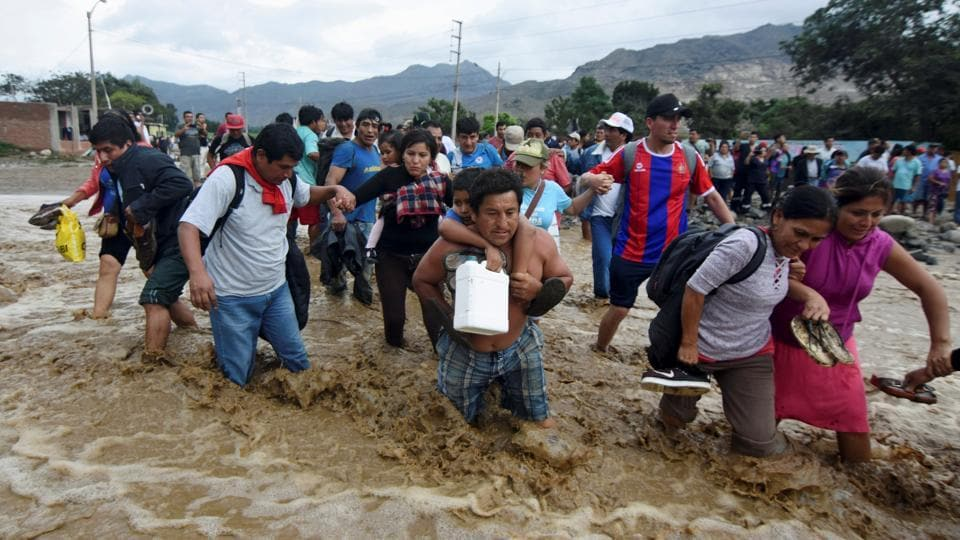 Residents cross a flooded street after a massive landslide and flood in Trujillo, northern Peru, March 17, 2017.