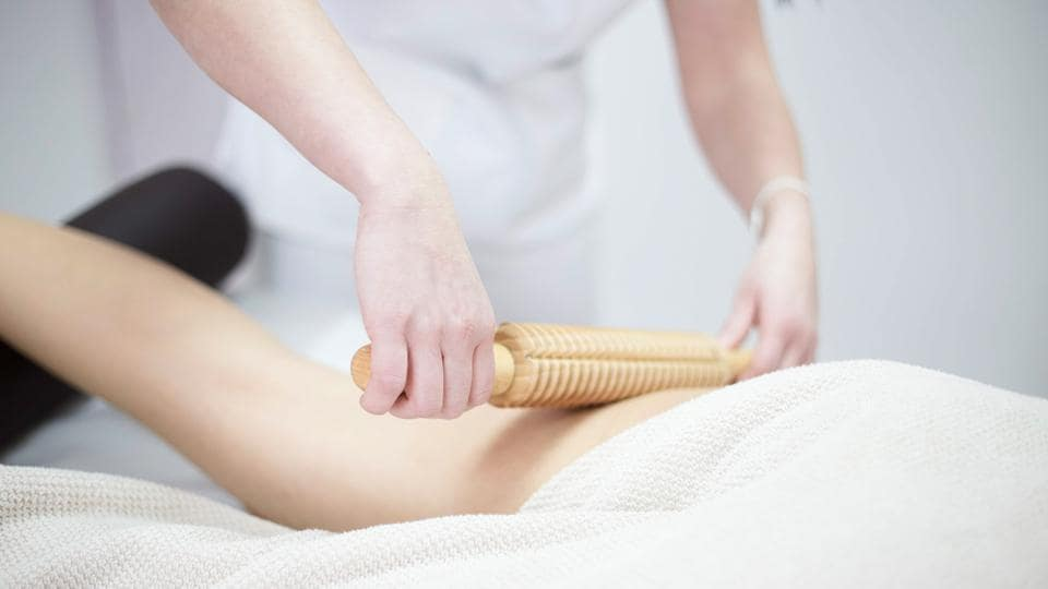 A woman gets an anti-cellulite massage with rolling pins.