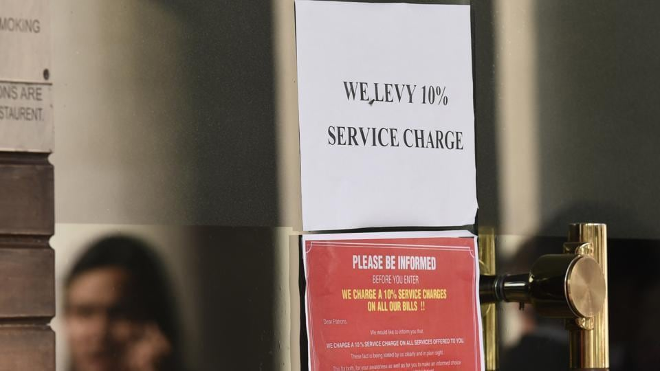 A restaurant in Connaught Place displaying a sign that service charges will be levied on the bill.