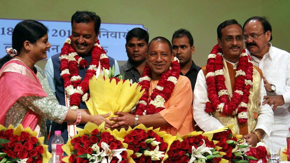 Union minister M Venkaiah Naidu (R), Uttar Pradesh BJP leaders Prasad Maurya (2L) and Dinesh Sharma (2R) look on as Yogi Adityanath (C) is presented with a floral bouquet during a ceremony in Lucknow on March 18, after he was picked as the new chief minister.