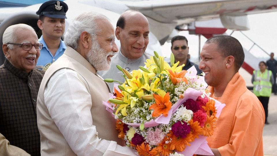 Prime Minister Narendra Modi being offered a bouquet by Yogi Adityanath, on his arrival in Lucknow, Uttar Pradesh on Sunday.