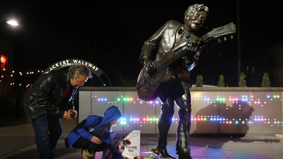 Paul Brown of Creve Coeur and his daughter Lacey Brown, 10, visit the statue of music legend Chuck Berry on the Delmar Loop,  on Saturday, in University City, Mo.