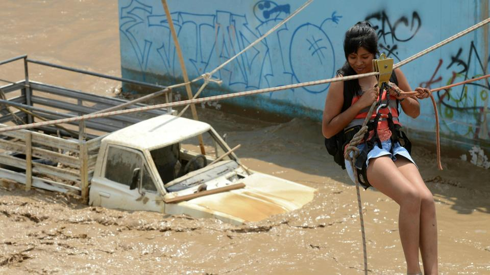 A resident of the Huachipa district, east of Lima, being helped to cross over flash floods.
