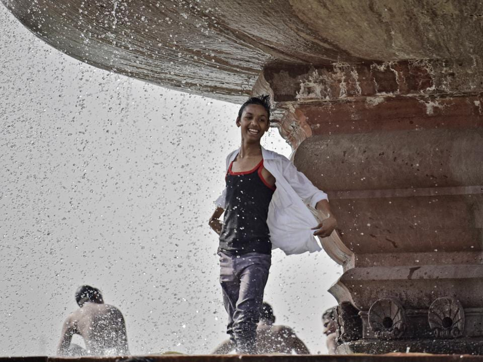 A boy enjoying in a water pond during the hot weather at India Gate. Temperatures will be scorching this week, says Met department.