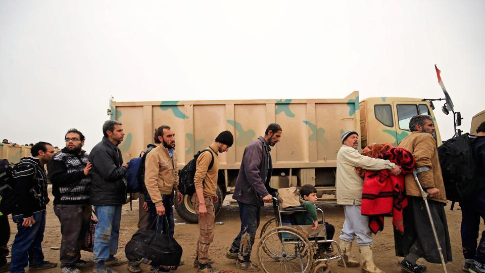 Displaced Iraqi people who fled their homes during a battle between Iraqi forces and Islamic State militants, arrive at a checkpoint to be transfer to Hammam al-Alil camp, in Mosul, Iraq, March 20, 2017.