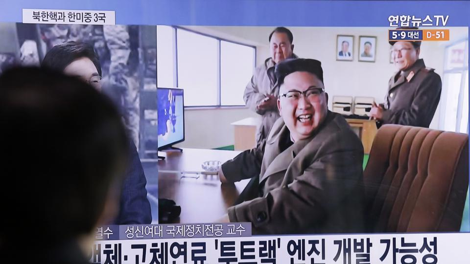 A man watches a TV news program showing an image, published in North Korea's Rodong Sinmun newspaper, of North Korean leader Kim Jong Un at the country's Sohae launch site, at Seoul Railway station in Seoul, South Korea.