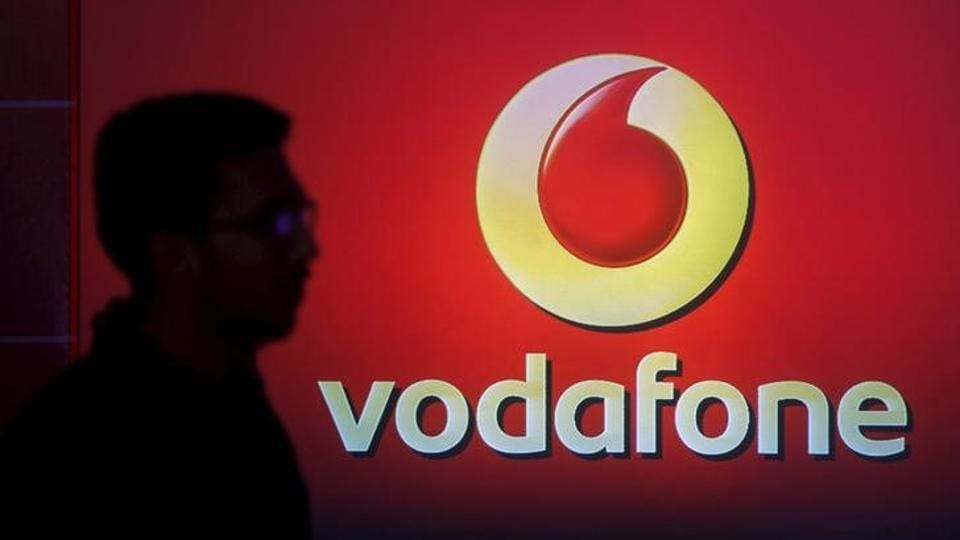 A man casts silhouette onto an electronic screen displaying logo of Vodafone India. The British telecom group  has decided to merge its Indian subsidiary with local rival Idea Cellular.