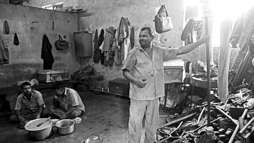 "Many trackmen live so far away from their worksites that going home every day is not an option. So they live in makeshift shelters called tapris. This is the inside of a tapri near Platform 6 of CST. The men take turns to do the cooking. ""I've made a 3 kg handi of pulao today,"" says Vijay Harpal (standing). ""We eat like tigers.""  (Pratik Chorge/HT PHOTO)"