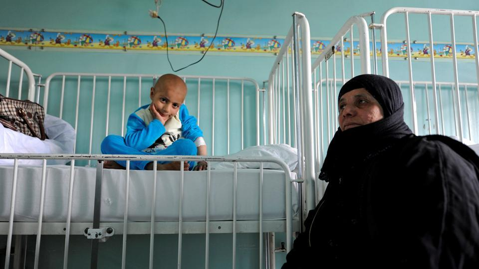 Syrian girl Rahma (L) sits on a bed next to her grandmother Um Ahmad, as she receives treatment for cancer. On top of this, cuts in health spending by the government that is fighting a hugely expensive war, a drastic fall in the Syrian currency and indirect effects of the sanctions are all deepening the misery of patients who need foreign-made drugs. (Omar Sanadiki/REUTERS)