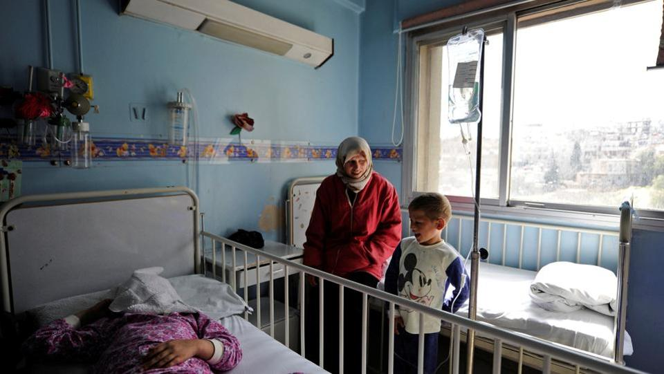 Syrian boy Ghazi (R) who receives treatment for cancer and his mother Um Ghazi (C) stand at the bed of another patient. However, a lack of cash is not the only reason why supplies of cancer drugs are falling far short of increasing demand. (Omar Sanadiki/REUTERS)