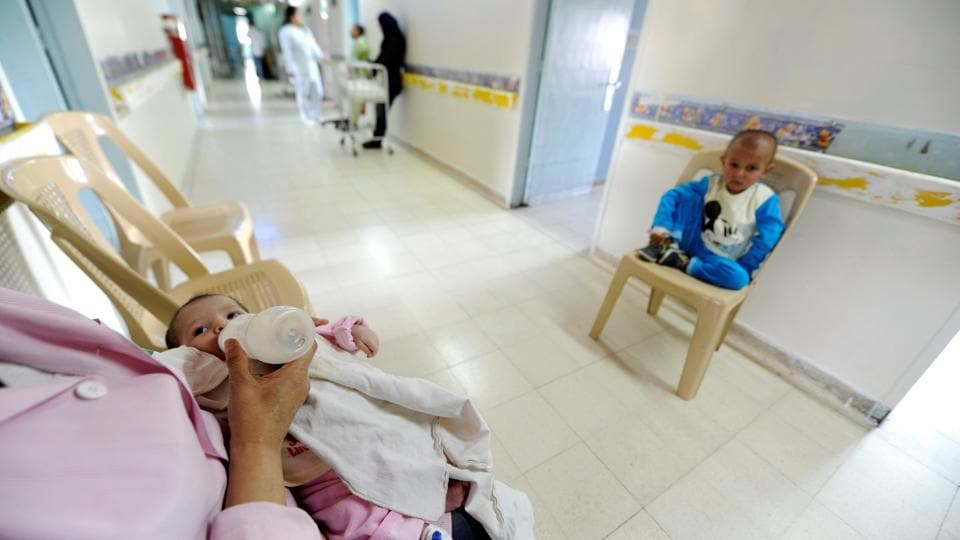 A nurse feeds a baby undergoing cancer tests, as another child with cancer sits on a chair. (Omar Sanadiki/REUTERS)