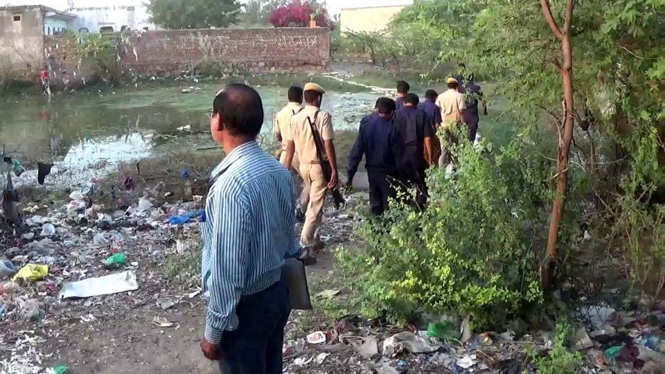 Police conduct search operations at a pond in Bharatpur in which several girls jumped in to avoid police detention.