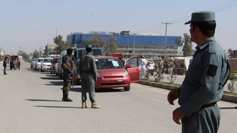 Afghan policemen inspect vehicles at a checkpoint in Helmand province, Afghanistan, in February 2017.