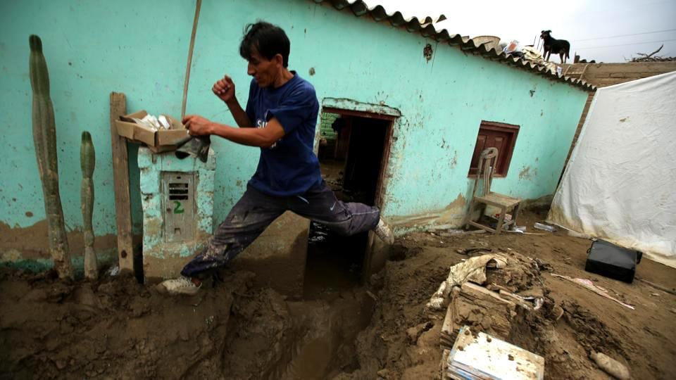 A resident jumps next to his destroyed home after rivers breached their banks due to torrential rains, causing flooding and widespread destruction in Cajamarquilla, Lima in Peru. (Mariana Bazo/REUTERS)