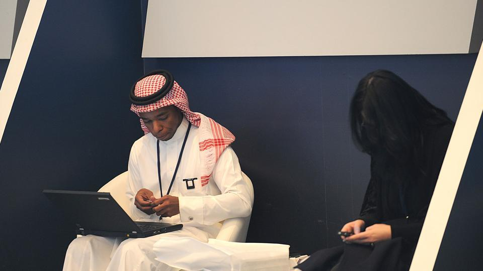 A Saudi man sitting near a woman as he works on his laptop at a hotel in Riyadh, Saudi Arabia. The United States is poised to ban large electronic devices such as laptops or cameras on board flights from up to a dozen Middle East nations.