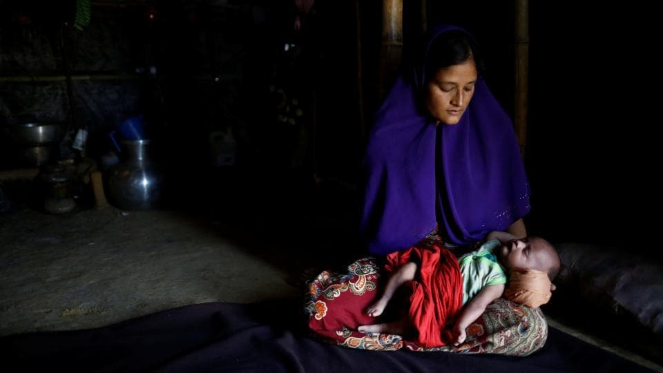 Rajuma Begum, 28, poses for a photograph with her one-month-old son Raihan inside their shelter in Kutupalang unregistered refugee camp in Cox's Bazar. 'I fled to Bangladesh because of fear, because I needed to save my children. I was pregnant and suffering from fever while crossing the border. I also have an 11-month-old boy, so it was very difficult to reach the border from our village Wabek in Myanmar. I had to rest frequently. After six hours of horrible walking finally we reached the border at 2am and crossed the border after paying a broker,' Rajuma Begum said.  (Mohammad Ponir Hossain/REUTERS)