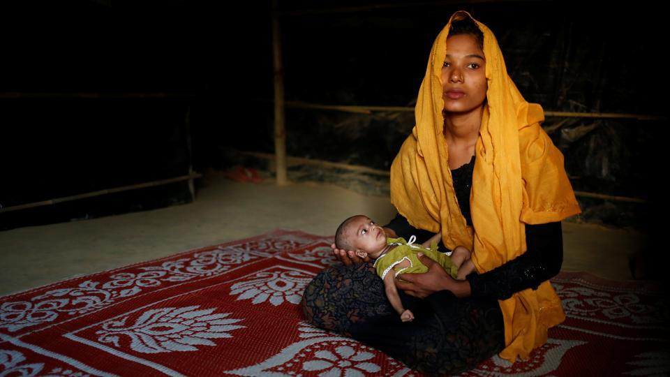 Sanwara Begum, 20, poses for a photograph with her 25-day-old daughter Aasma inside their shelter in Kutupalang unregistered refugee camp in Cox's Bazar. Sanwara Begum fled to Bangladesh from Khyeri Prang village in Myanmar, with her husband around two and a half months ago. Her husband Rafiqullah now works as a day labourer in Cox's Bazar. 'No one wants to leave their own home. We have come to Bangladesh only to save our lives. Myanmar is our home, we will move to Myanmar immediately if the situation becomes stable,' Sanwara said.  (Mohammad Ponir Hossain/REUTERS)
