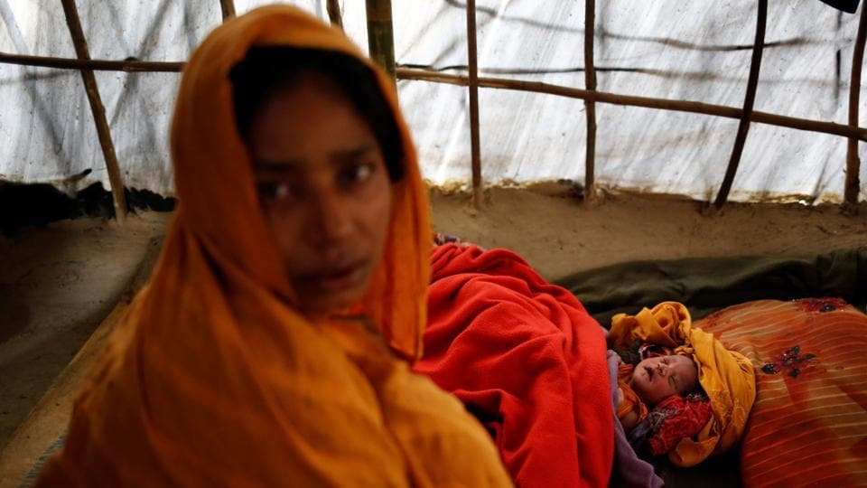 Noor Begum, 26, sits next to her one-day-old daughter Sumaiya as she poses for a photograph inside their shelter in Balukhali unregistered refugee camp in Cox's Bazar. Noor Begum came to the camp one-and-a-half months ago from Nagpura village with her husband Jahangir Alom. (Mohammad Ponir Hossain/REUTERS)