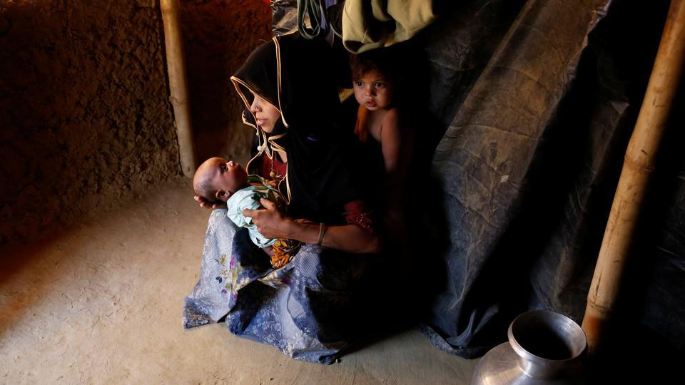 Marijaan, 20, holds her 25-day-old daughter Noor Habi as her son stands inside their shelter in Kutupalang unregistered refugee camp in Cox's Bazar. Marijaan fled to Bangladesh from Khyeri Prang village in Myanmar one month ago after her house was burnt down the by Myanmar military. 'I reached the border at night and crossed by the boat. I paid the boatman to cross the Naf River,' Marijaan said. (Mohammad Ponir Hossain/REUTERS)