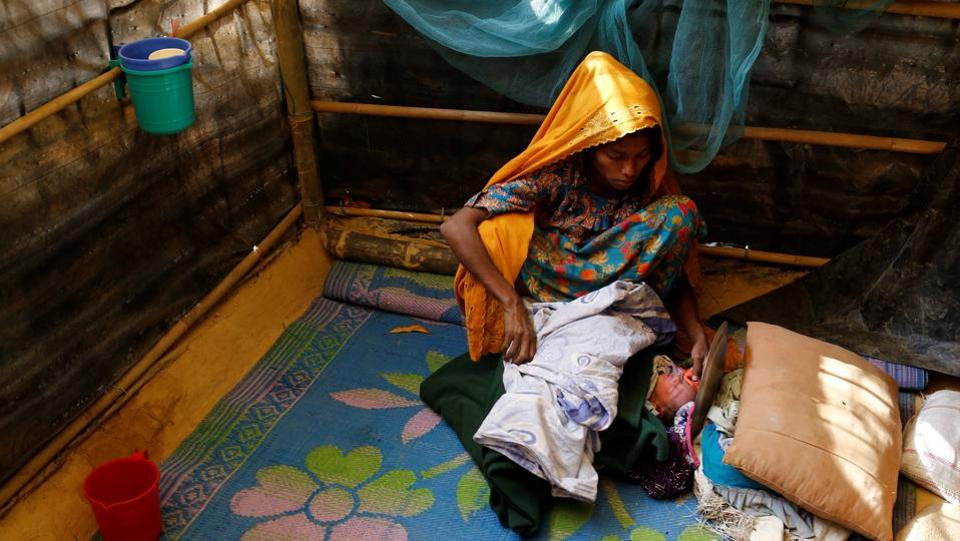 Fatema, 25, sits beside her one-day-old daughter Aasma in Kutupalang unregistered refugee camp in Cox's Bazar, Bangladesh, February 9, 2017. Fatema fled to Bangladesh from Jambuinna village in Myanmar two months ago after her house was burnt down by the military. She crossed Naf River by boat during the night. 'Our situation is better than many other refugees as my husband Mohammad Alom works here as a day labourer. Many of the new refugees have no work here, so they have to rely on relief,' Fatema said. (Mohammad Ponir Hossain/REUTERS)