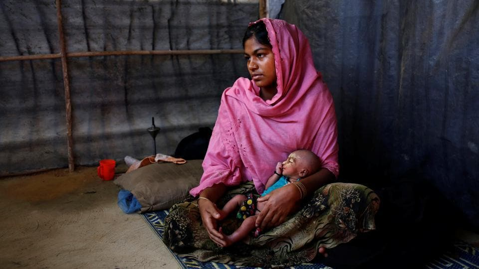 Asmot Ara, 18, holds her seven-day-old unnamed daughter as she poses for a photograph inside their shelter in Balukhali unregistered refugee camp in Cox's Bazar, Bangladesh. Asmot Ara said she came to the camp one month ago with neighbours from Nagpura village in Myanmar after her father-in-law was killed and their home burnt down by the Myanmar military. (Mohammad Ponir Hossain/REUTERS)