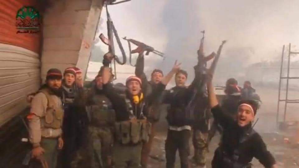 A still image taken from a video uploaded on social media on March 20, 2017, shows fighters, said to be members of Ahrar Al Sham group, holding up their weapons and cheering, said to be in Damascus, Syria.