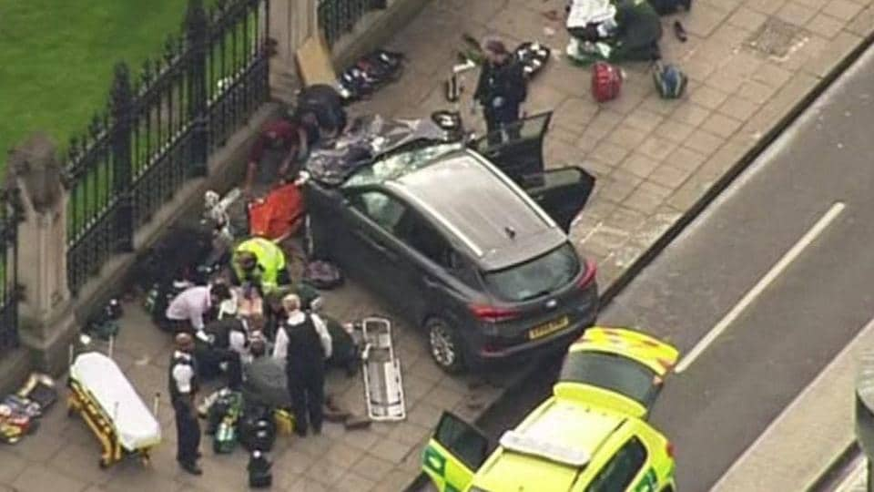 In this image taken from video police officers gather around a car adjacent to Houses of Parliament in London, Wednesday, after the House of Commons sitting was suspended as witnesses reported sounds like gunfire outside.