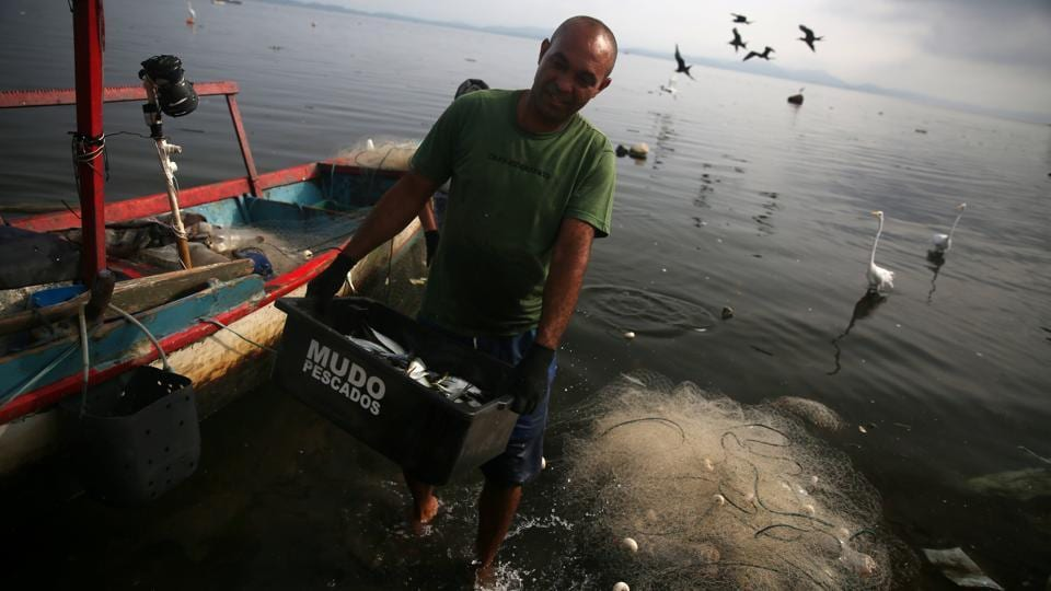 A fisherman carries a box of fishes at the Bancarios beach, ahead of World Water Day, in the Guanabara bay in Rio de Janeiro, Brazil. (Pilar Olivares / REUTERS)