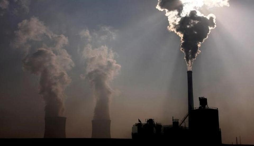A coal-burning power plant can be seen behind a factory in the city of Baotou, in China's Inner Mongolia Autonomous Region.
