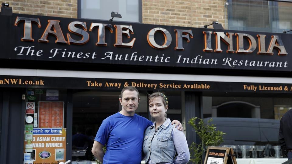 Polish engaged couple Pawel Bednarek, a builder, and Aga Pozniak, who teaches training courses for adults, pose for photographs outside where they work part-time to supplement their incomes, at the Taste of India curry restaurant in London on March 9, 2017.