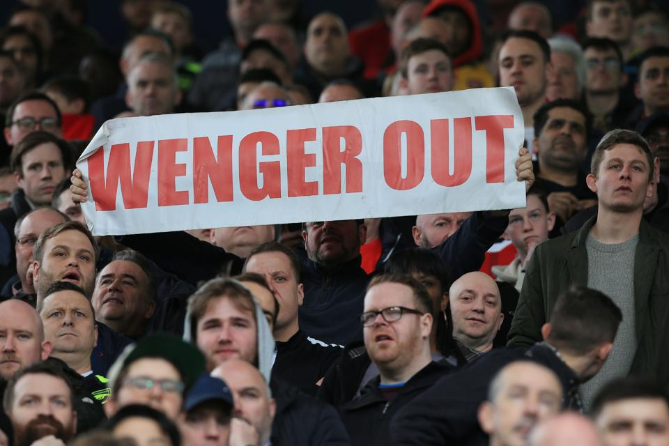 A fan holds up an anti-Arsene Wenger sign during the English Premier League football match between West Bromwich Albion and Arsenal at The Hawthorns stadium in West Bromwich, March 18, 2017.